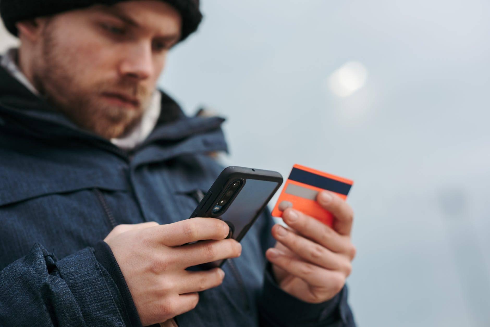 Mężczyzna płacący kartą w telefonie online